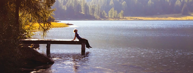 Person sitting at the end of a dock in scenic surroundings; QAI helps protect the environment through organic certification.
