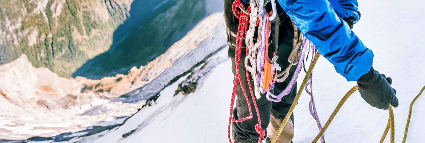 Mountain climber with climbing gear. Reach your organic certification goals with QAI.